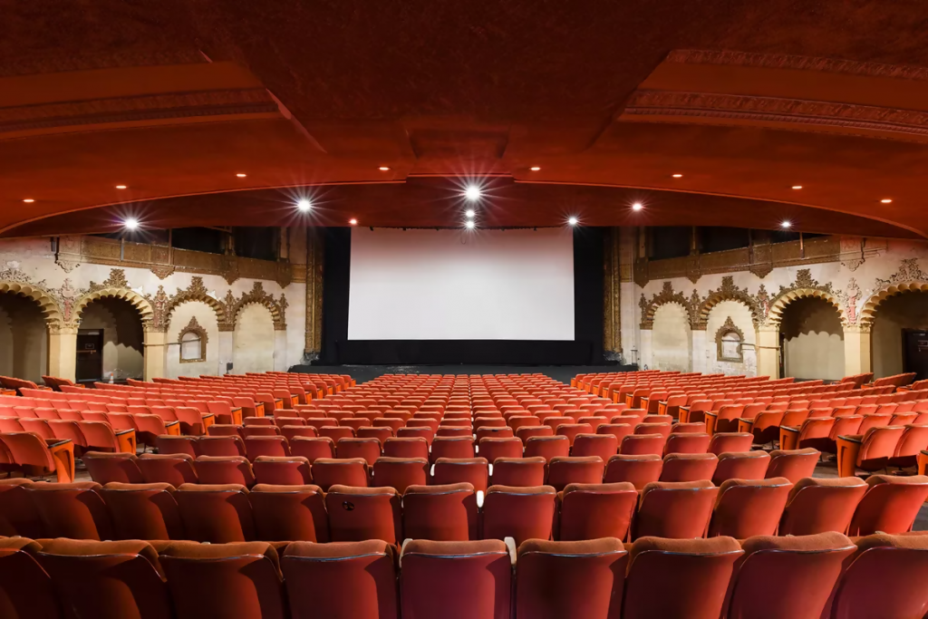 rows of empty seats in front of a screen inside hollywood pacific theatre